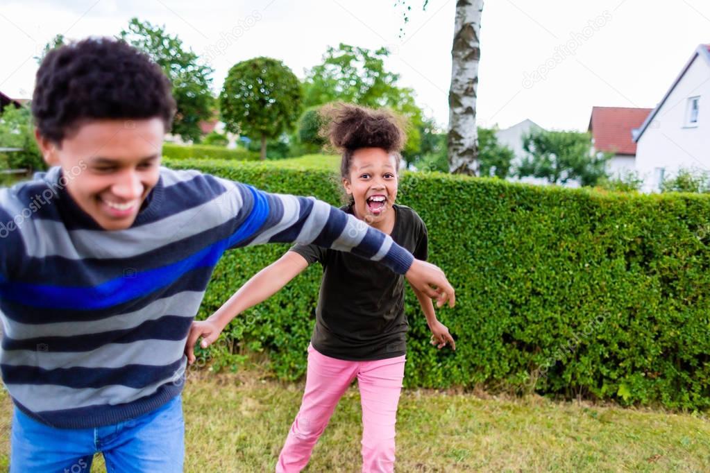 Siblings playing in garden