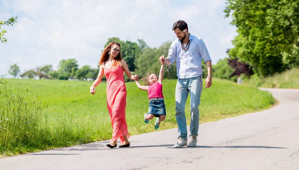 Family letting kid fly in summer walk