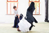Fotografie Man and woman having Aikido stick fight