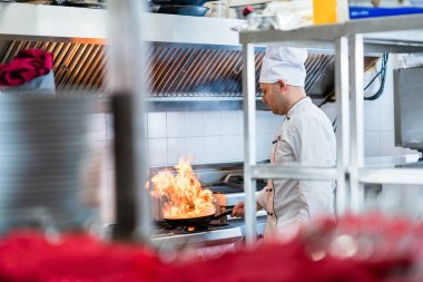 Chef or cook in hotel kitchen cooking dishes