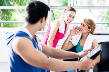 sportive man on treadmill flirting with smiling girls