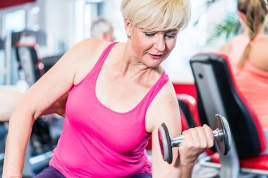 senior woman working out with dumbbell