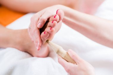 Women at reflexology having foot massaged