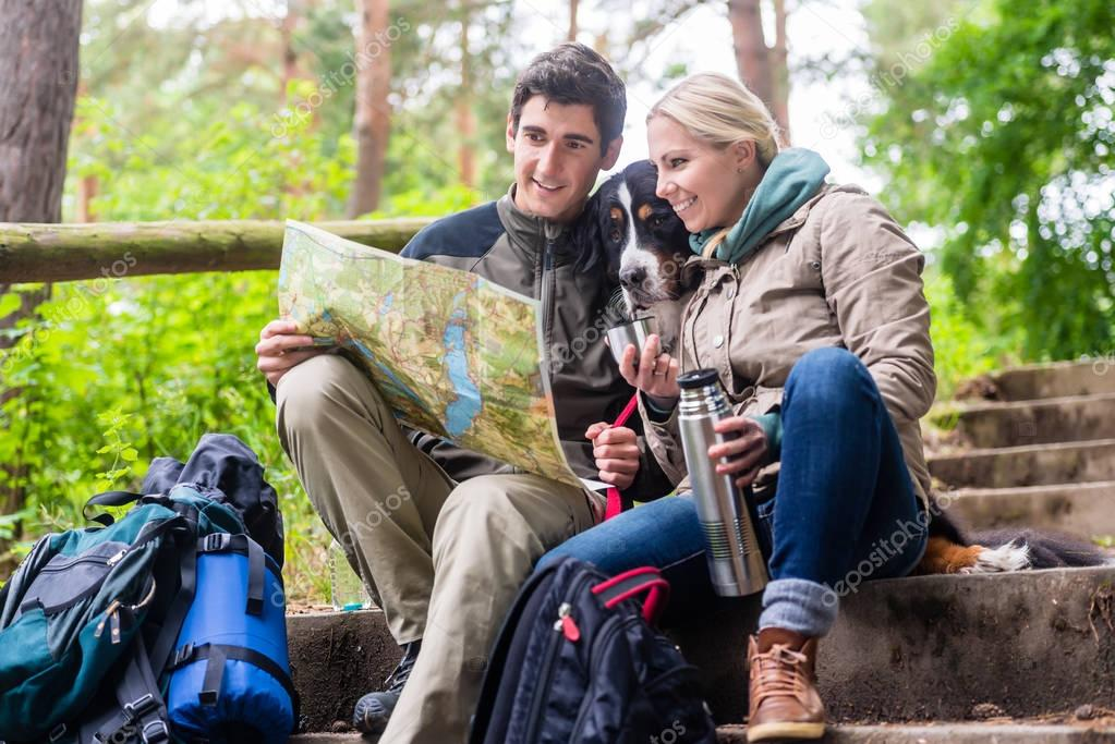 Man and woman on hike planning next route section on map