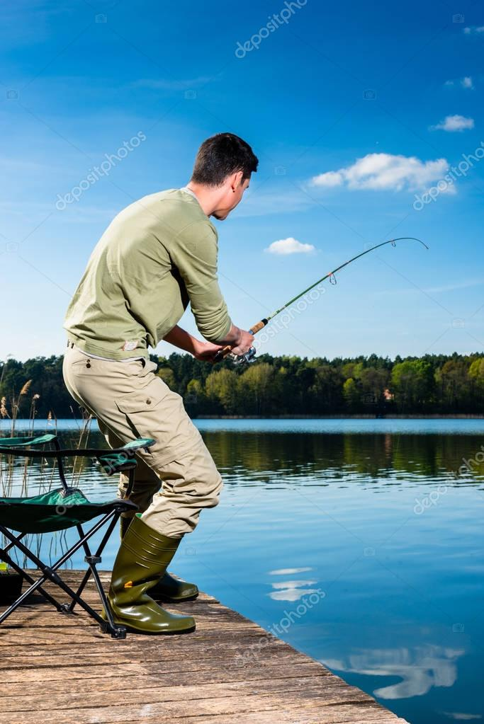 Angler fishing at lake standing on jetty