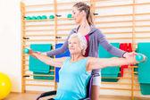 Starší žena v invalidním vozíku dělá fyzikální terapie