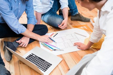 Team of architects sitting on floor with construction plans