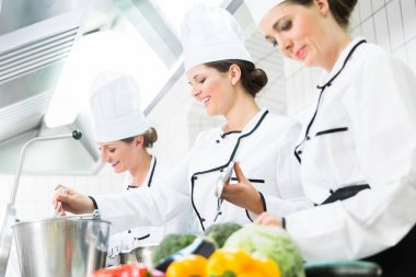 chefs preparing meals in commercial kitchen