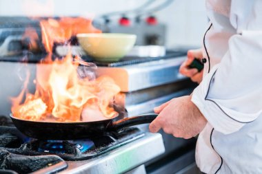 Chef doing flambe to dish in pan