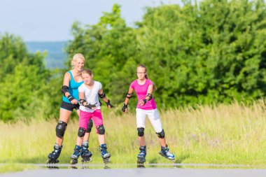 Family rollerblade with skates on country lane