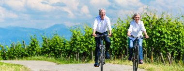 Seniors riding bicycle in vineyard together