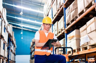 Asian man in industrial warehouse