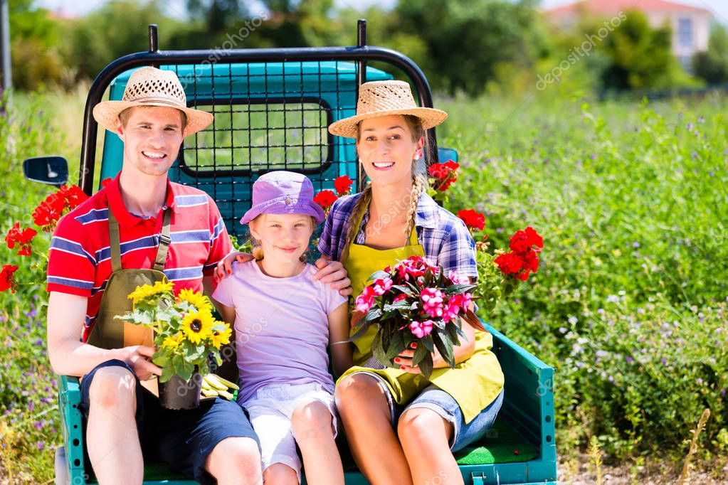 Family on light truck with flowers