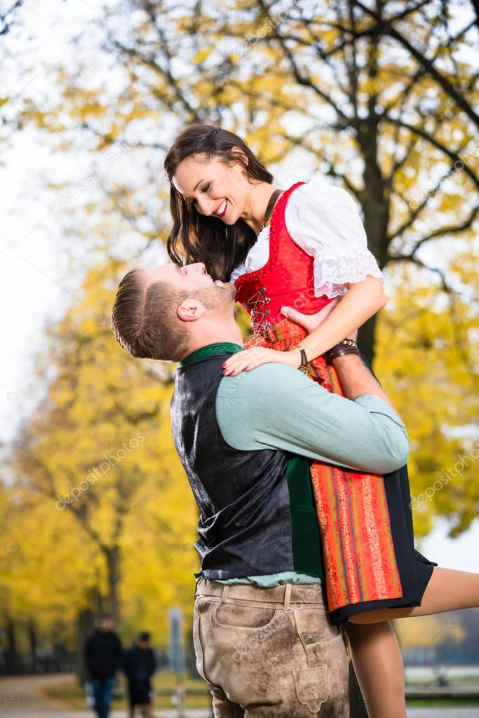 Bavarian couple in Tracht in loving embrace with uplift