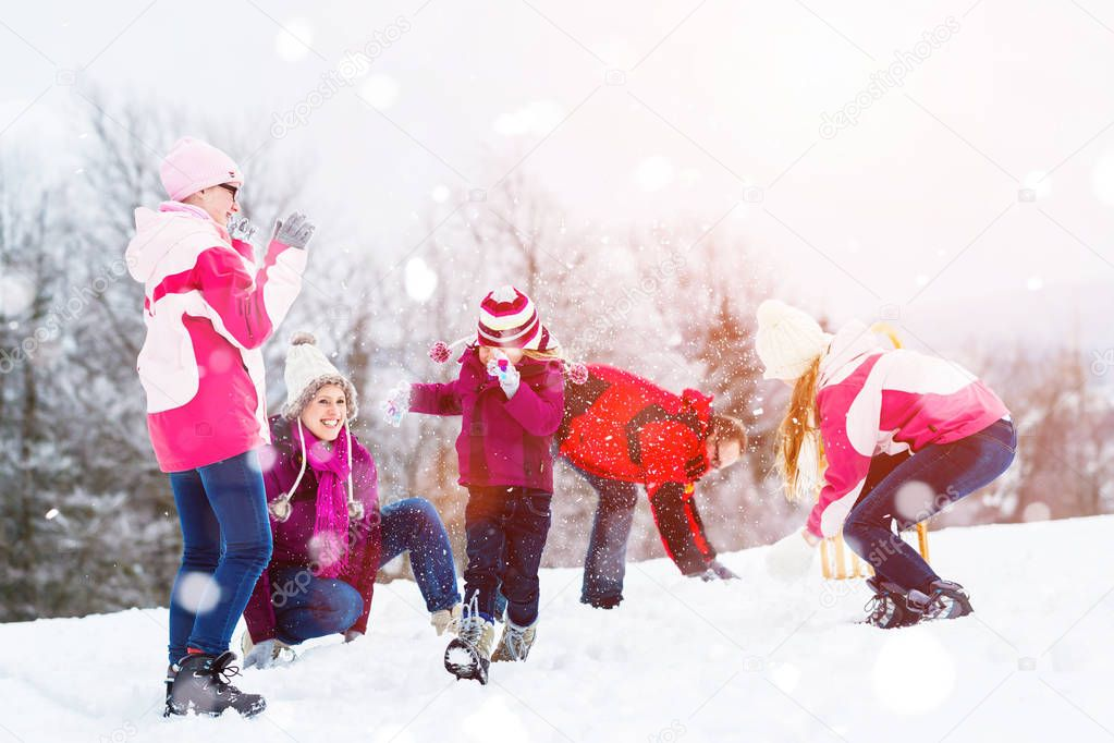 Family playing in snow having fight with snowballs