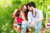Rodina jí v letní louce sedí na trávě