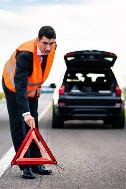 Man with car breakdown erecting warning triangle