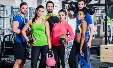 Group of women and men in gym posing at fitness training