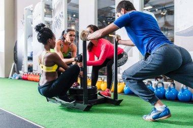 Man pushing women on cart as fitness exercise