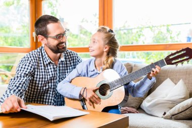 Father and daughter learning play the guitar