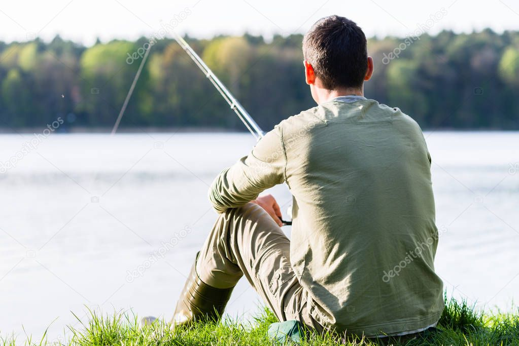 Angler sitting in grass at lake fishing with his rod
