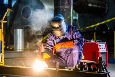 Welder working in industrial factory