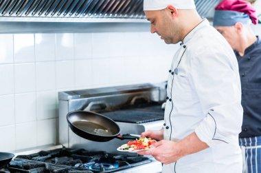 Chefs in restaurant kitchen cooking