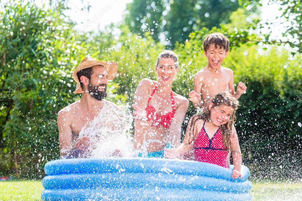 Family cooling down splashing water in garden pool