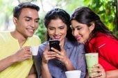 Fotografie Indische Mädchen zeigen Bilder auf Handy an Freunde