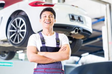 Car mechanic working in Asian Chinese auto workshop
