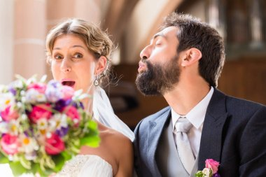 Groom trying to kiss bride