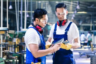 Asian worker checking work piece in production plant
