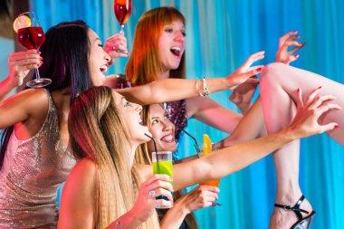 Drunk girls with fancy cocktails in strip club