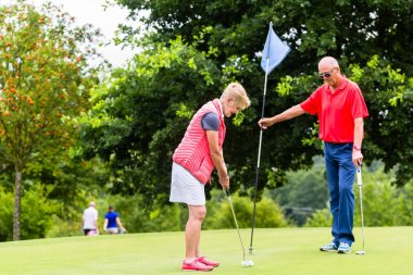 Senior woman and man playing golf