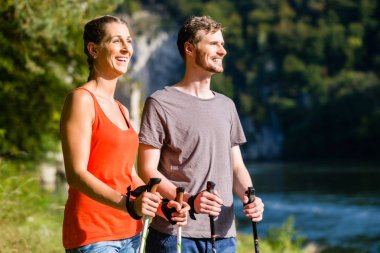 Man and woman hiking at river in summer