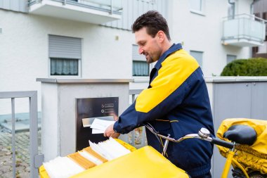 Postman delivering letters to mailbox