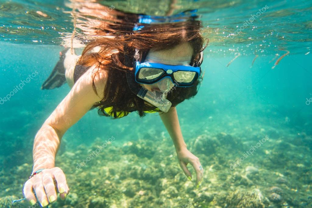 Woman snorkelling over floor of tropical sea
