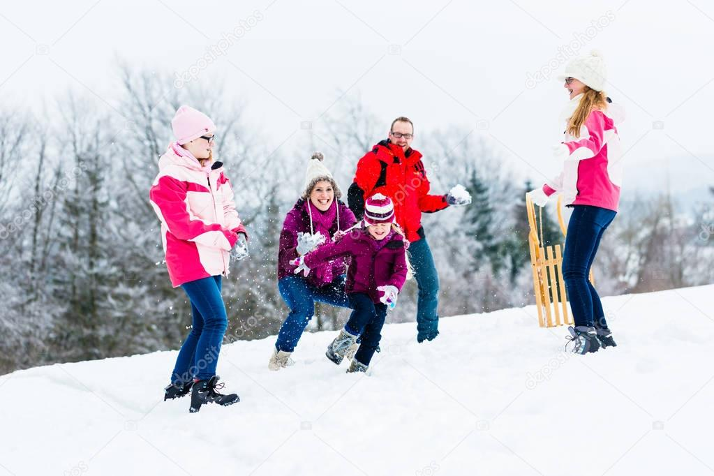 Family with kids having snowball fight in winter