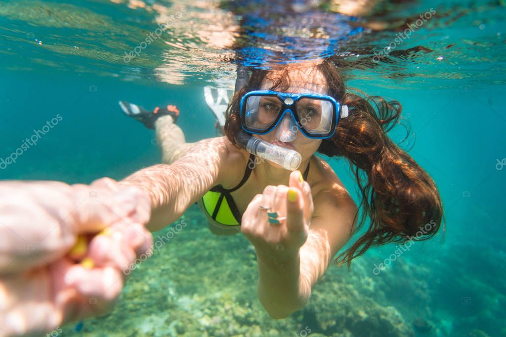 Snorkelling woman makes tempting gesture in ocean