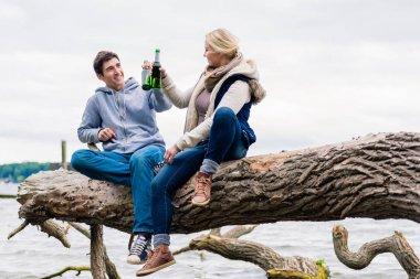 couple sitting on tree stump