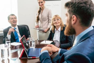 Confident managers listening to younger colleague