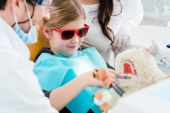 Photo Child at dentist office looking after teeth of pet toy