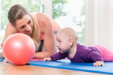 Mom and baby practicing to crawl in mother and child course