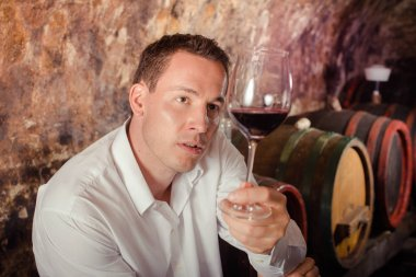 man tasting wine in cellar