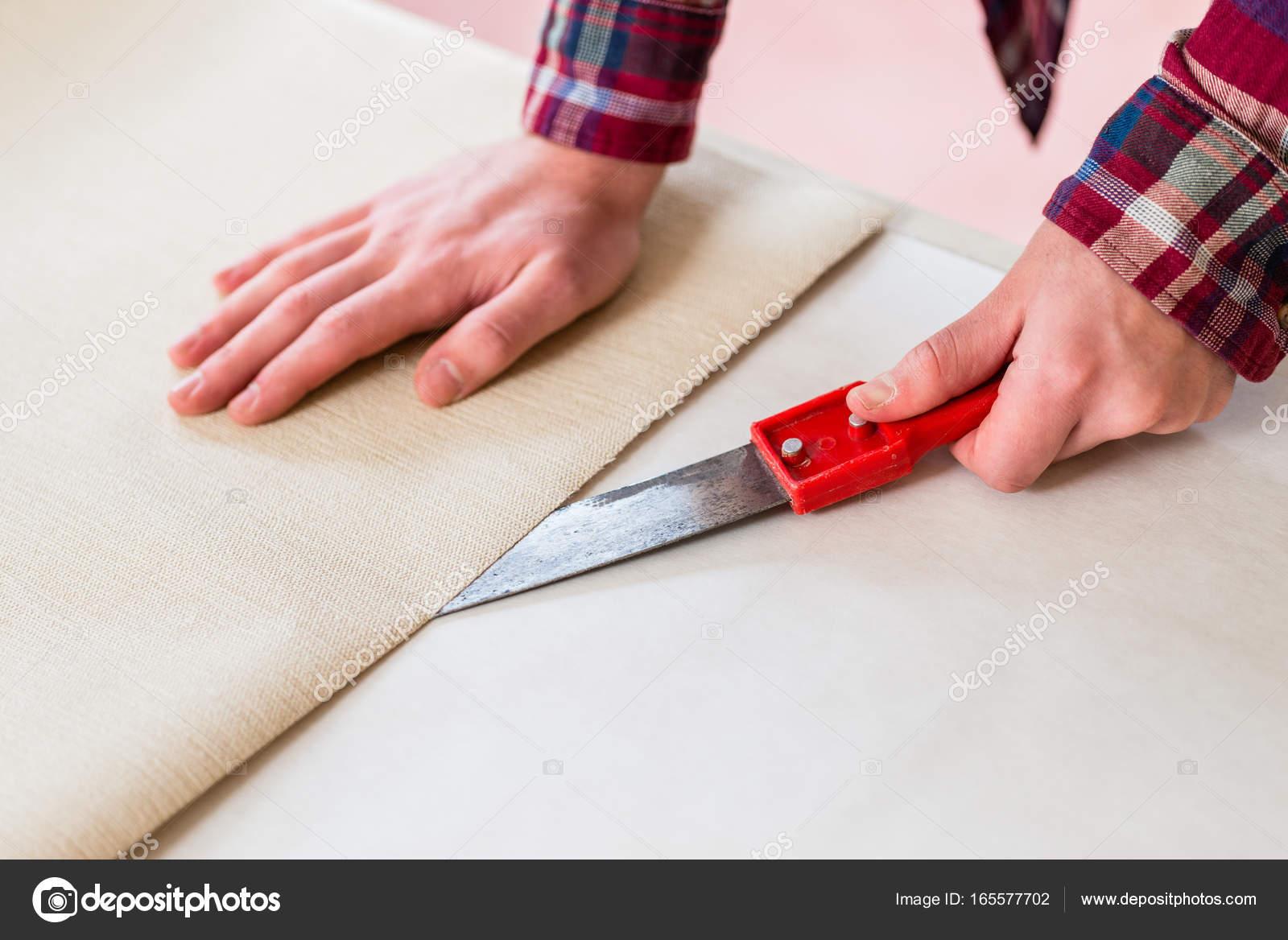 nahaufnahme von den händen eines mannes schneiden eine neue tapete