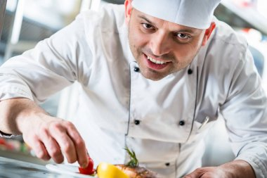 Chef garnishing the food on plate to complete the dish