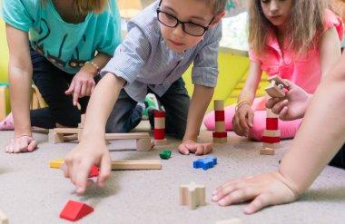 Female educator teaching children to build a train circuit durin