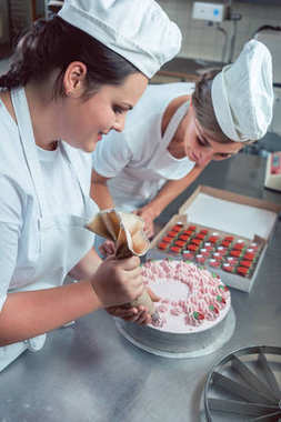 Confectioner women putting cream on cake