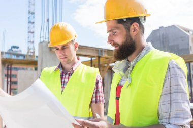 Two young construction workers wearing yellow hard hats and reflective safety vests while analyzing together the plan of a new building stock vector