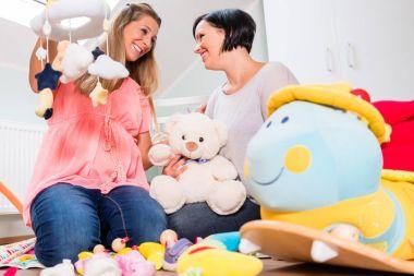 mother and friend preparing nursery